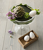 Incomplete Easter flower arrangement with artichokes and eggs