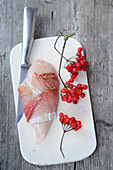 Raw chicken breast wrapped in bacon next to a sprig of guelder rose berries