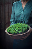 A woman holding a bowl of fresh cress