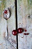 Kirschen, Granatapfelkerne und alter Löffel auf Holzuntergrund