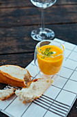 A glass of pumpkin soup next to a piece of white bread