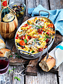 Pasta bake with tomatoes, olives, oregano and Parmesan with baguette and red wine