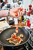 Tomaten zu Rindfleisch in den Wok geben