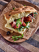 Focaccia with tomato, olives and rocket