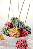 Different coloured popcorn balls on sticks