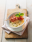 Cream of garlic soup with a pork belly skewer