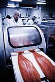 Fliessband in Fischfabrik zur Verpackung von Lachsseiten
