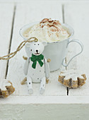 Hot chocolate with cream with a Christmas bear and cinnamon biscuits in front of it