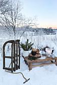 Rustikaler Holztisch mit Geschirr und Weihnachtsdekoration und Holzschlitten im Schnee