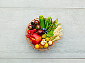 Fresh, colourful fruit and vegetables in a wire basket (seen from above)