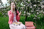 Mädchen beim Picknick auf Wiese unter Apfelbäumen