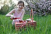 Mädchen giesst Saft in Glas beim Picknick auf Wiese unter Apfelbäumen