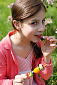 A girl eating a fruit skewer at a picnic amongst apple trees