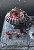 A chocolate wreath cake with bananas and strawberries