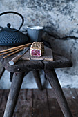 Unsliced tuna fish tataki on a rustic wooden stool (Japan)