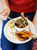 Frau isst geschmorte Lammkeule mit Feta-Kräuter-Brösel, Kürbis und Möhren mit Kräutern aus dem Ofen, Kartoffel-Artischocken-Püree und ein Mini-Zucchinigratin