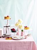 Tortelettes mit frischen Himbeeren auf romantisch gedecktem Tisch
