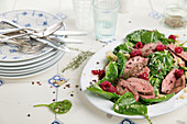 Roast duck breast on a spinach salad with raspberries
