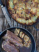 Beef steak in broth with onions and fried potatoes
