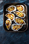 Grilled oysterstopped with bechamel sauces grated cheese, sliced garlic and parsley