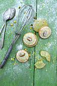 Iced pistachio biscuits on a green wooden surface