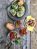 Erbsen-Hummus, Blätterteig mit Karotten und gebackenen Tomaten auf rustikalem Holztisch