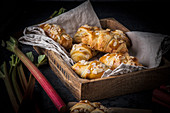 Rhubarb croissants on a linen cloth in a wooden crate (Denmark)