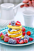 Ricotta pancakes with cream and frozen berries