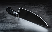A meat knife with a sharp blade on a grey background