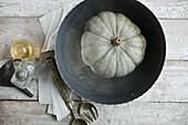 A Crown Prince pumpkin in a metal bowl