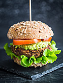Vegan red beans and quinoa burger sandwich with guacamole, fresh lettuce and tomatoes, served on a whole grain bun