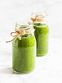 Two small bottles of healthy vegan green smoothie, made with baby spinach and kale