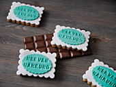 Biscuits with fondant decorations and chocolate on a wooden board