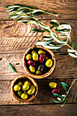 Various olives in a wooden bowl next to olive sprigs (seen from above)