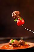 Fleischbällchen mit Tomate auf Gabel gespiesst