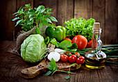 Stillleben mit frischem Gemüse, Kräutern und Olivenöl in Karaffe