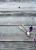 A wooden surface with a vintage teaspoons and flowers
