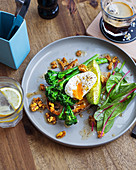 Toast with broccolini, poached egg, avocado and walnuts