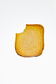 A slice of zwieback (rusk) with a bite missing, on white background