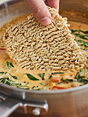 Mie noodles being placed in oriental soup
