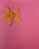 A star made of pasta shapes on a pink surface