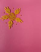 Stern aus kurzen Röhrennudeln gelegt auf rosafarbenem Untergrund