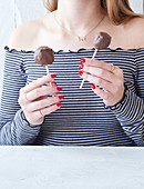 A woman holding two sugar-free banana bread cake pops