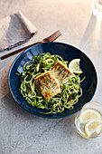 Crispy fish fillet on a bed zoodles