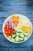 Chopped raw vegetables and sweetcorn in a bowl