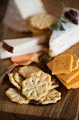 Crackers and various types of cheese on a wooden board