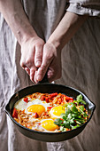 Traditional Israeli Cuisine dishes Shakshuka (Fried egg with vegetables tomatoes and paprika in cast-iron pan in female hands)