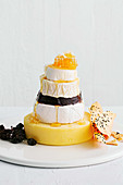 A stack of cheese with dried fruit, unleavened bread and honey