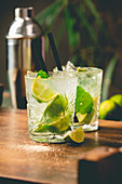 Two glasses of mojito cocktail with fresh lime and mint on a wooden table