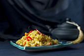 No-meat pilaf garnished with red chili peppers on a dark blue background